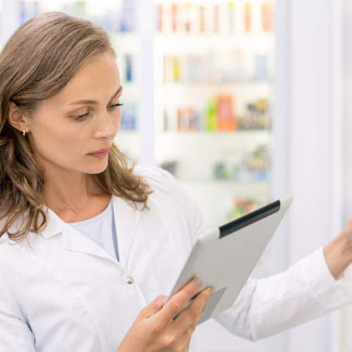 Young pharmacist with touchpad checking or looking for new medicine in computer base while standing by one of displays in drugstore